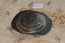 Silver belt buckle with Aztec calendar, front